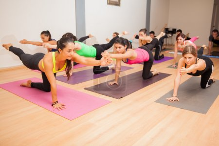 Photo pour Portrait d'une enseignante de yoga enseignant un cours de yoga à un grand groupe de personnes - image libre de droit