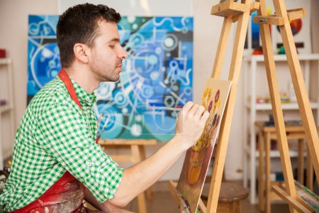 Photo for Profile view of a good looking young artist enjoying his work as an artist and working on a painting in his studio - Royalty Free Image