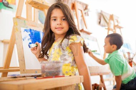 Hispanic girl holding a paintbrush