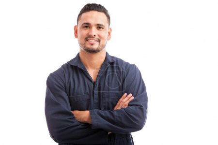 Photo for Young Hispanic mechanic wearing overalls and smiling with his arms crossed - Royalty Free Image