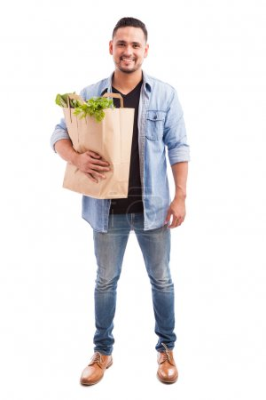 Photo for Full length view of a young man carrying a bag of groceries while dressing casually against a white background - Royalty Free Image