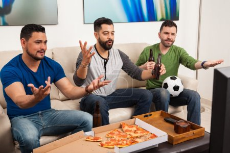 Photo for Group of three gruys watching a soccer game on TV and yelling at the screen because of an unfair play - Royalty Free Image