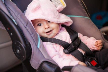 Photo pour Portrait d'une belle petite fille assise sur un siège d'auto et souriant - image libre de droit