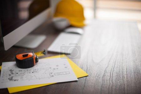 Photo pour Informatique, construction plans, helment et ruban à mesurer en l'espace de travail de l'architecte avec faible profondeur de champ - image libre de droit