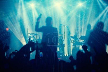 Photo pour Silhouettes de personnes et de musiciens en grande scène de concert. Lumineux beaux rayons de lumière - image libre de droit
