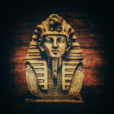 Stone pharaoh tutankhamen mask on papyrus backgrou...