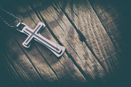 Silver cross on a wood background