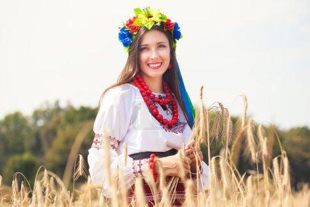 Photo pour Belle jeune femme portant des vêtements ukrainiens nationaux posant dans le champ de blé - image libre de droit