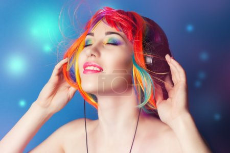 Photo for Beautiful woman wearing colorful wig and headphones against blue background - Royalty Free Image
