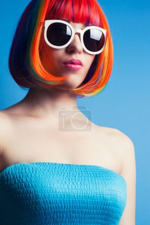 Photo for Beautiful woman wearing colorful wig and white sunglasses against blue background - Royalty Free Image