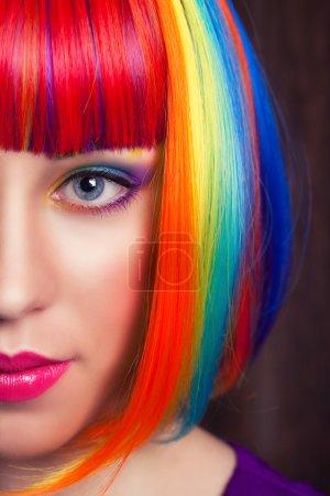 Foto de Hermosa mujer lleva peluca colorida y mostrando coloridas uñas contra fondo madera - Imagen libre de derechos