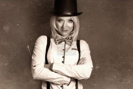 Photo pour Belle jeune femme portant un chapeau haut de forme et un nœud papillon avec des bretelles sur fond gris - image libre de droit