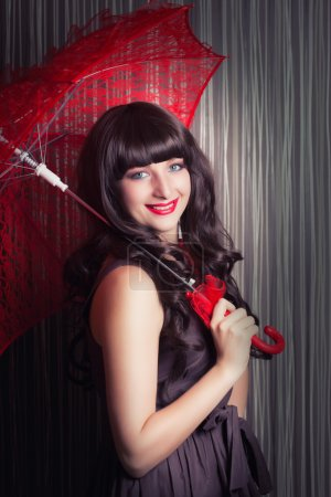 Woman posing with red lace umbrella