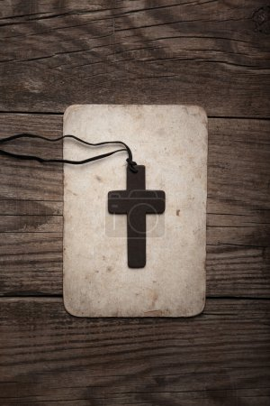Photo for Wooden cross on paper isolated on brown  background - Royalty Free Image