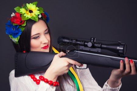 Photo pour Belle jeune femme portant des vêtements nationales ukrainiens et tenant un fusil - image libre de droit