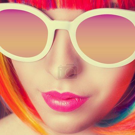 Photo pour Belle femme portant une perruque colorée et des lunettes de soleil blanches gros plan - image libre de droit