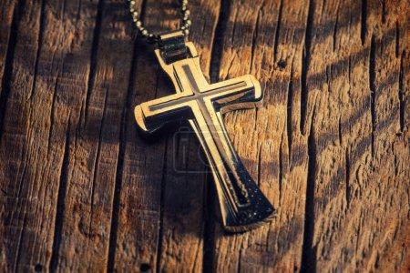 Photo pour Gros plan de croix d'argent sur fond en bois - image libre de droit
