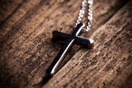 Foto de Primer plano de la cruz de plata sobre un fondo de madera - Imagen libre de derechos