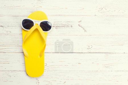 Photo pour Flip flop jaune et lunettes de soleil sur fond de bois blanc - image libre de droit