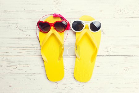 Photo for Yellow flip flops and sunglasses on a white wooden background - Royalty Free Image