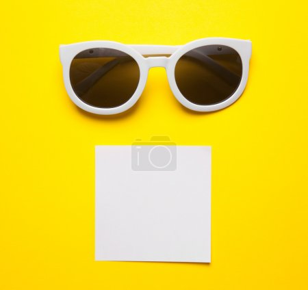 White sunglasses on yellow background