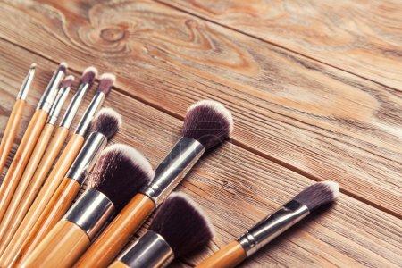 Photo pour Ensemble de pinceaux pour maquillage dispersés chaotiquement sur fond en bois - image libre de droit