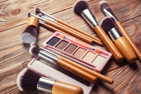 Photo for Brushes with cosmetics scattered chaotically on wooden background - Royalty Free Image