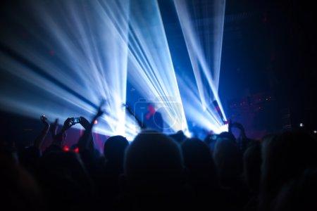 Photo pour Silhouettes des personnes et des musiciens en scène grand concert - image libre de droit