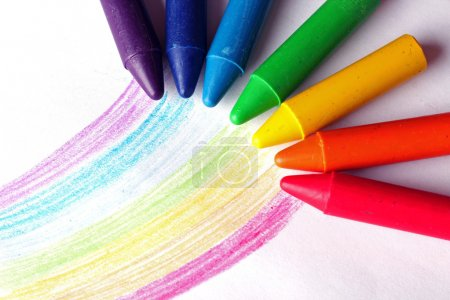 Oil pastel crayons lying on a paper with painted rainbow. Selective focus