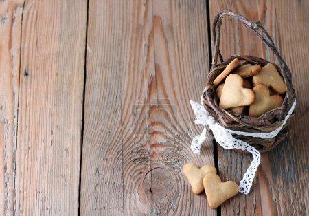 Photo pour Vacances, amour, concept de nourriture et de boisson. Biscuits faits à la main pour la Saint-Valentin dans un panier sur une table en bois. Concentration sélective - image libre de droit