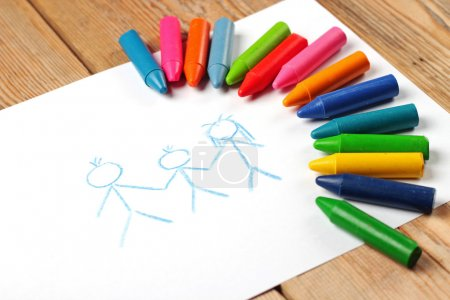 Crayons lying on a paper with children's drawing f...