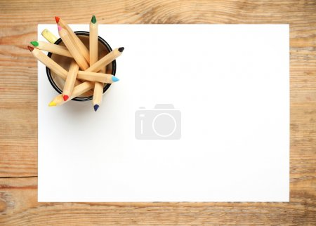 Still life, business, education concept. Pencils in a mug with sheet of paper on a wooden table. Selective focus, copy space background, top view