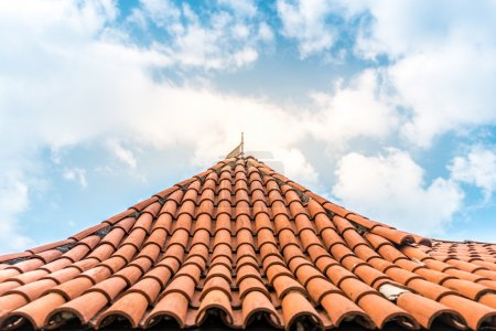 Old tiled roof with sky in background