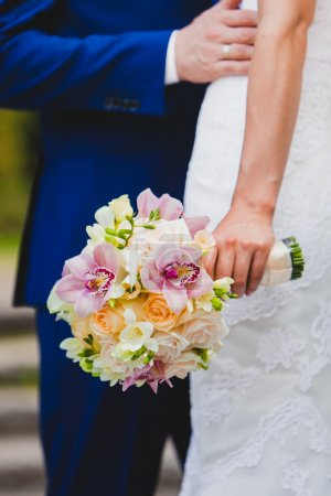 Close up of bride holding beautiful wedding flowers bouquet with orchid