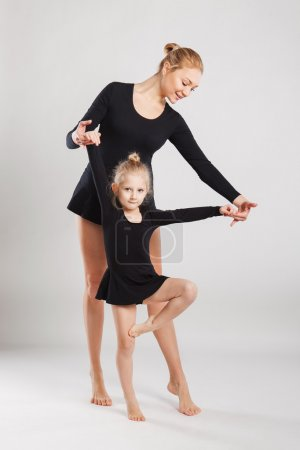 Mom teaching daughter dancing. Daughter and mother gymnastics
