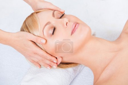 Young attractive beautiful woman getting spa treatment over white background