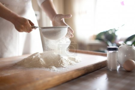 young woman sifting flour into bowl at the kitchen