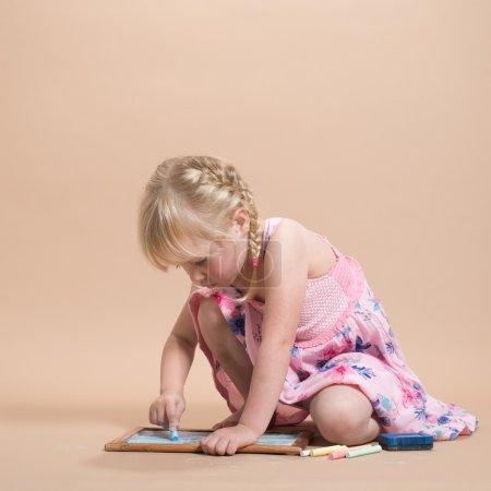 Photo pour Petite fille absorbée dans le jeu avec ses craies colorées et tableau noir - image libre de droit