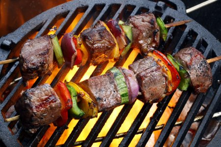 Kebabs with vegetables on grill