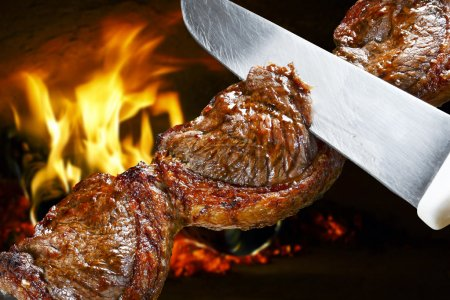 Photo for Man hands cutting Picanha, traditional Brazilian barbecue. - Royalty Free Image