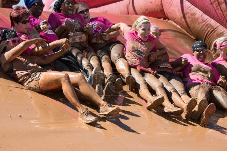 Group Of Muddy Women Hold Hands Sliding Into Mud Pit