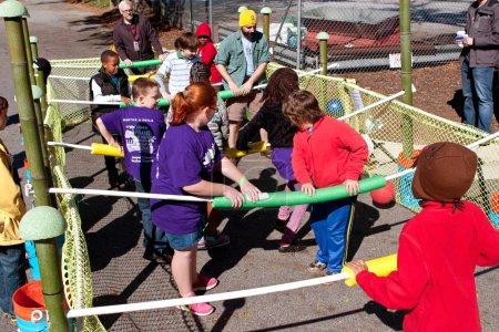 Photo pour Decatur, Ga, Usa - 4 octobre 2014: Les enfants et les adultes jouent à un jeu de foosball humain à l'annuel Maker Faire Atlanta. - image libre de droit