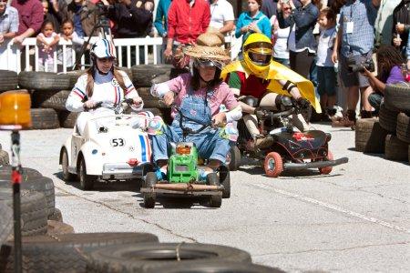 Menschen rasen mit motorisierten Miniaturfahrzeugen auf Macher-Messe