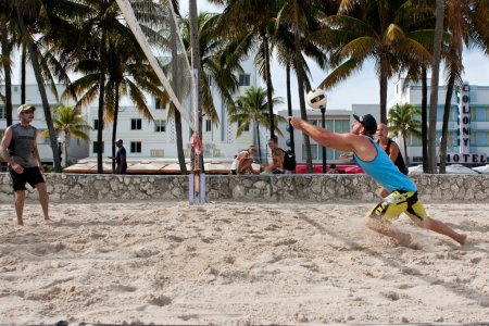 Photo pour Miami, FL, USA - December 27, 2014:  A man lunges to pass the ball in a pickup game of beach volleyball on a public beach off Ocean Drive in Miami. - image libre de droit