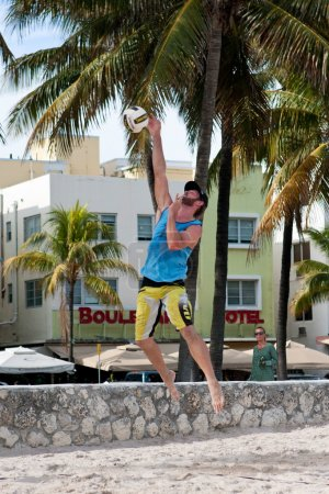 Photo pour Miami, FL, USA - December 27, 2014:  A man hits a strong jump serve in a pickup game of beach volleyball on a public beach off Ocean Drive in Miami. - image libre de droit