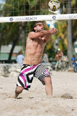 Photo pour Miami, FL, USA - December 27, 2014:  A man uses his extended arms to pass the ball in a pickup game of beach volleyball on a public beach off Ocean Drive in Miami. - image libre de droit