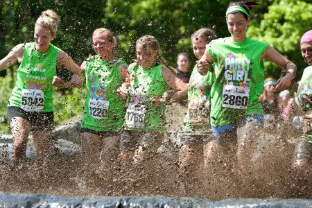 Photo pour Atlanta, GA, USA - April 28, 2012: A group of young women join arms and stomp through a mud pit together at The Dirty Girl Mud Run in Atlanta. - image libre de droit