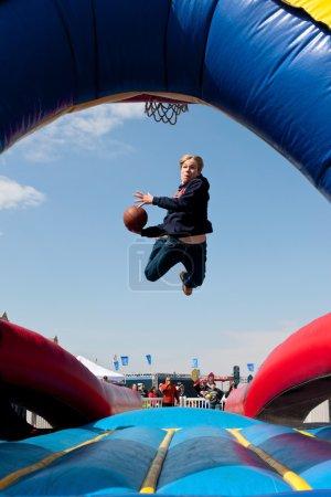 Photo pour Hampton, Ga, é.-u. - 28 février 2015 : Un adolescent utilise un mini-trampoline à décoller lors d'une tentative de dunk un ballon de basket dans un jeu de carnaval. - image libre de droit