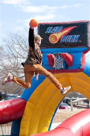 Photo pour Hampton, Ga, é.-u. - 28 février 2015 : Un adolescent utilise un mini trampoline pour s'envoler au-dessus de la jante lors d'une tentative de dunk un ballon de basket dans un jeu de carnaval. - image libre de droit