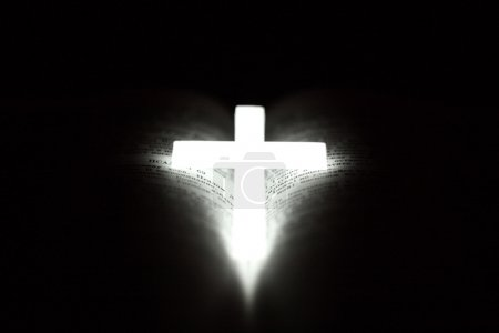 Photo for Glowing phosphor Christian cross on open Bible - Royalty Free Image